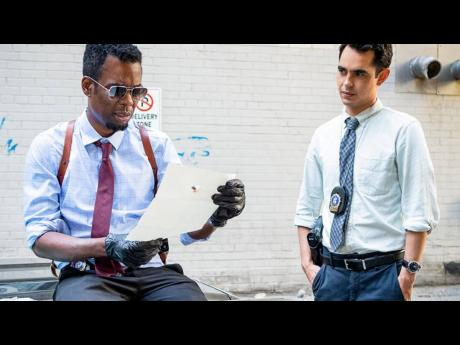 Chris Rock (left) and his rookie partner Max Minghella in a scene from the horror film 'Spiral'.