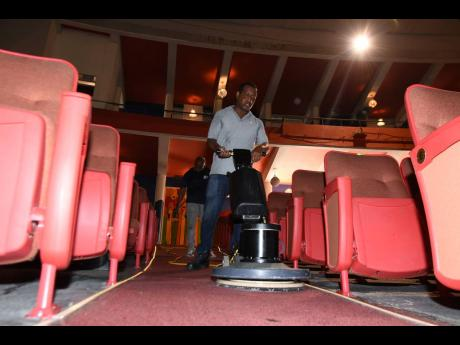Michael Ebanks from Manpower and Maintenance Services Limited cleans the carpets of the Little Theatre.