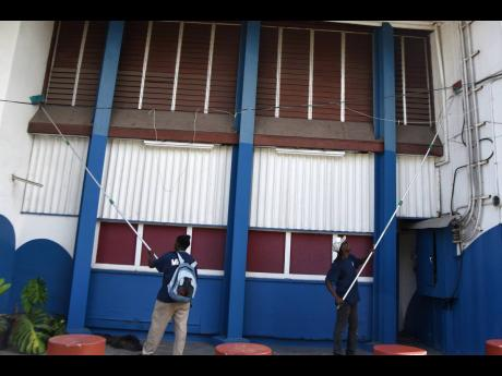 Workmen from Manpower and Maintenance Services Limited were seen cleaning the walls of the Little Theatre on Arthur Wint Drive ahead of the reopening of the entertainment industry.