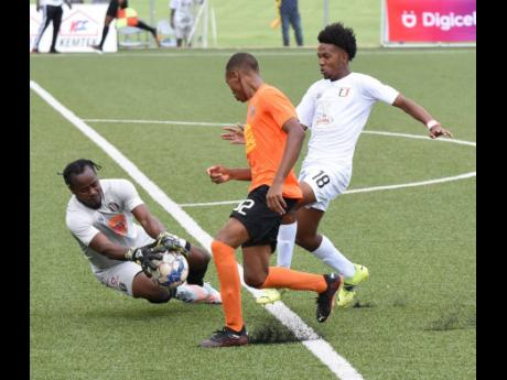 Tivoli Gardens' Odean Pennycooke (centre) blocks off the onrushing Shadane Lopez (right) of Arnett Gardens, so his goalkeeper Kewong Watkins can grab the ball during their Jamaica Premier League match at the UWI/JFF/Captain Horace Burrell Centre of Excel