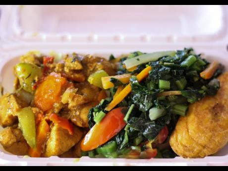 A neatly boxed meal of curried chicken, steamed callaloo on top of boiled food with a side of fried ripe plantain would satisfy any Jamaican breakfast craving.