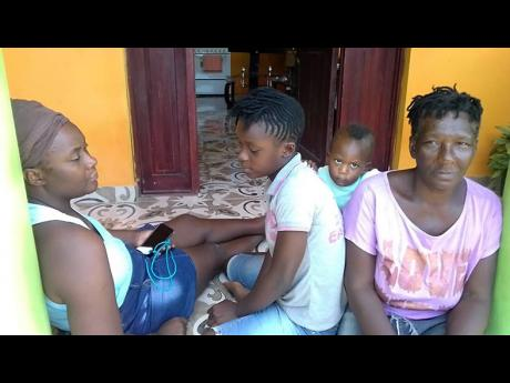 Lisa Medley (left), sister of the late Fabian Medley, sits with his daughter, Akelia (centre), and mother Iris Rashford as they reflected on the shooting death in New Town, St Elizabeth.