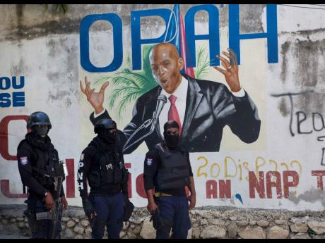 Police stand near a mural featuring Haitian President Jovenel Moïse, near the leader's residence where he was killed by gunmen in the early morning in Port-au-Prince, Haiti, on Wednesday, July 7.