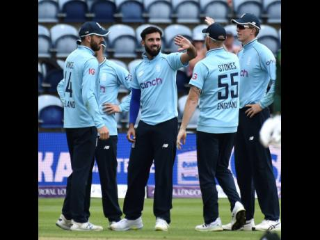 England's Saqib Mahmood (centre) celebrates with teammates after dismissing Pakistan's Faheem Ashraf during the first One-Day International cricket match against Pakistan at Sophia Gardens in Cardiff, Wales, yesterday.
