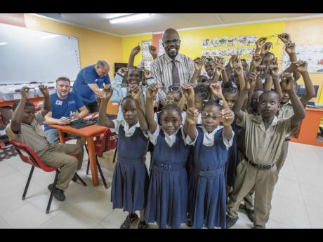 ABOVE: Volunteers of the Issa Trust Foundation look on as principal Martin Murphy of Free Hill Primary and his excited students show off their new glasses received through 'Vision Mission'.