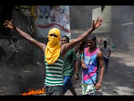People protest against the assassination of Haitian President Jovenel Moïse near the police station of Petion Ville in Port-au-Prince, Haiti.