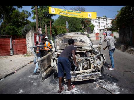 People try to recover usable material from a burned-out car during a protest a day after the murder of President Jovenel Moïse in Port-au-Prince, Haiti.