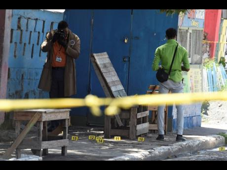 In this June 2021 photo, investigators are seen processing a crime scene in Trench Town.