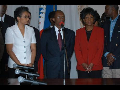 Jean Bertrand Aristide and his wife Mildred (left) address a press conference on February 21, 2004 at Haiti's presidential palace eight days before he was ousted as president. On the right is US Congresswoman Maxine Waters.