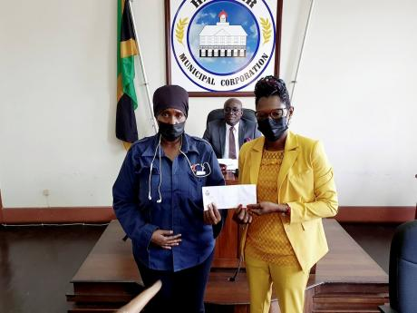 Hanover municipal police officer, Nicole Bookal (left), accepts a cash award for her professional services from Deputy Mayor of Lucea Councillor Andria Dehaney-Grant, while Lucea Mayor Sheridan Samuels (centre) looks on.