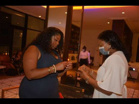 Tareka Coney (left) exchanges business cards with Odette Dyer, regional manager, Jamaica Tourist Board.