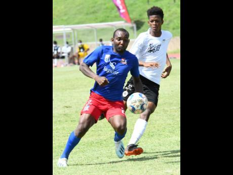 Dunbeholden's Rondee Smith (left) brings the ball under control while being monitored by Cavalier's Richard King during their Jamaica Premier League game at Stadium East in St Andrew yesterday.