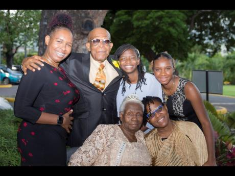 From left (back row) Rochelle Stephenson, Bishop Rupert Stephenson, Tiandre Stephenson, Kimberly Fearon, and Pastor Pauline Stephenson (left, front row) and Tannecia Stephenson celebrate the happy occasion.