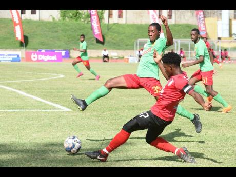 Arnett Gardens' Romeo Guthrie (front) whips in a cross which Humble Lion's Rico Evans tries to block during their Jamaica Premier League match at Stadium East, yesterday.