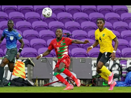 Jamaica full back Amari'i Bell (right) looks on as Suriname forward Sheraldo Becker whips in a cross during the second half of their Concacaf Gold Cup Group C match in Orlando, Florida, yesterday. The Reggae Boyz won the game 2-0.