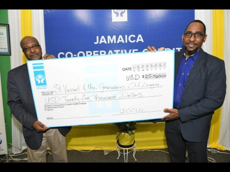 Oneil Grant (right), second vice-president Jamaica Co-operative Credit Union League (JCCUL), presents a cheque to the immediate past president of Caribbean Confederation of Credit Unions (CCCU), Winston Fletcher, recently.  Jamaica's credit unions rallie