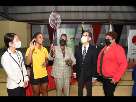 Minister of Culture, Gender, Entertainment and Sport Olivia Grange (third left) displays one of the 80 badminton rackets donated by the Japan Badminton Association to the Jamaica Badminton Association on July 8 at the Japanese Embassy in St Andrew. The don