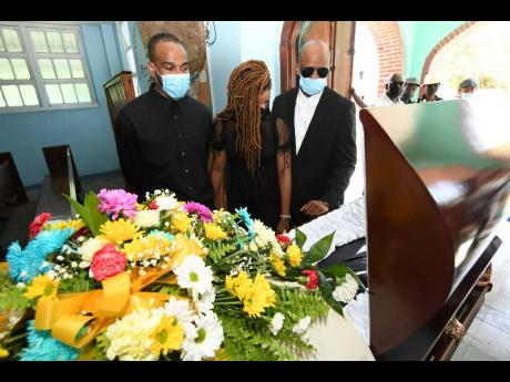 Orville Clarke's three children, Ryan (left), Latoya (centre) and Anthony, take a final look at his body during yesterday's funeral at the Holy Rosary Church in east Kingston.
