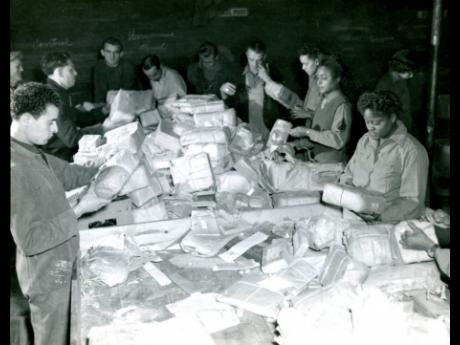 In this photo provided by the US Army Women's Museum, members of the 6888th battalion sort mail with French civilians in Rouen, France, in 1945.