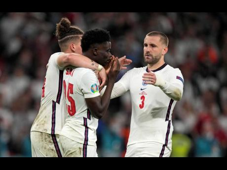 England's Bukayo Saka (centre) is comforted after he missed to score the last penalty during the penalty shootout of the Euro 2020 soccer championship final between England and Italy at Wembley stadium in London, Sunday, July 11.