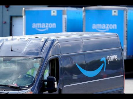 The Amazon Prime logo appears on the side of a delivery van as the Amazon Warehouse location in Dedham, Massachusetts.