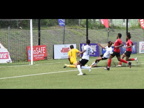 Arnett Garden's Goalkeeper Chadeem Rodriques (left) watches as a shot from Shaniel Thomas (centre) of Cavalier rolls into his net during their Jamaica Premier League game at the UWI/JFF Captain Horace Burrell Centre of Excellence in St Andrew yesterday.