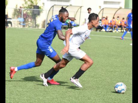 Mount Pleasant's Alwayne Harvey (right) is chased by Molynes United's Jermy Nelson during their Jamaica Premier League game at the UWI/JFF Captain Burrell Centre of Excellence on Sunday afternoon.