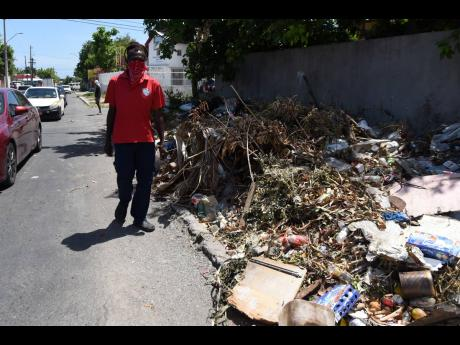 A pedestrian walks near the line of traffic on Monday because a sidewalk along Waltham Park Road, near the intersection of Bowens Road, has been transformed into a dump site. Residents of the St Andrew community have claimed that the National Solid Waste M