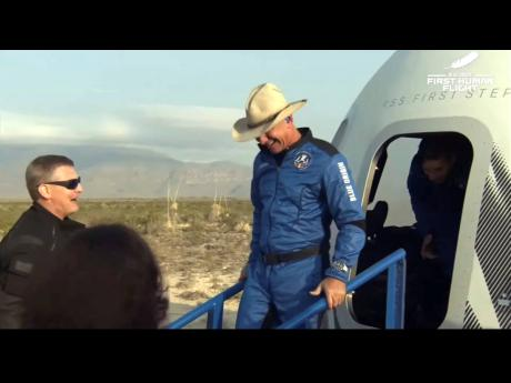 In this photo provided by Blue Origin, Jeff Bezos, founder of Amazon and space tourism company Blue Origin, exits the  Blue Origin's New Shepard capsule after it parachuted safely down to the launch area near Van Horn, Texas, Tuesday, July 20, 2021.