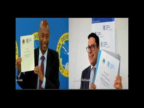 Caribbean Development Bank President Dr Gene Leon (left) and European Investment Bank Vice-President Mourinho Felix Ricardo show off the agreement signed to assist regional countries acquire vaccines.