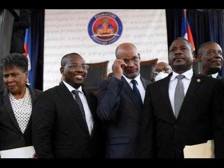 Ariel Henry (centre) and interim Prime Minister Claude Joseph (second left) stand with other members of the Cabinet during Henry's appointment as the new prime minister in Port-au-Prince, Haiti, yesterday.