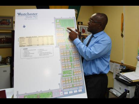 Portmore Mayor Leon Thomas discusses the layout of a WIHCON town house development for Westchester, Portmore.