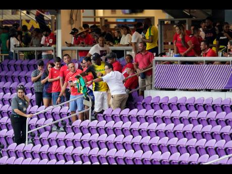 A marshall (left) ushers fans from their seats to shelter as a thunderstorm approaches the Exploria Stadium in Orlando, Florida yesterday.
