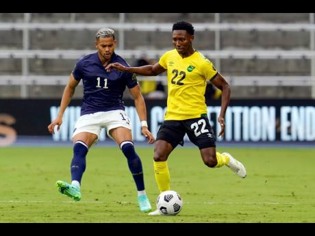 Jamaica midfielder Devon Williams (right) moves the ball past Costa Rica forward Ariel Lassiter during the first half of their Concacaf Gold Cup Group C match yesterday.