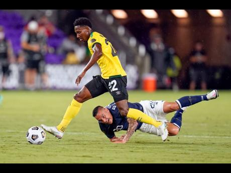 Jamaica midfielder Devon Williams moves the ball past Costa Rica midfielder David Guzmán (on ground) during the first half of their Concacaf Gold Cup Group C match in Orlando, Florida on Tuesday night.