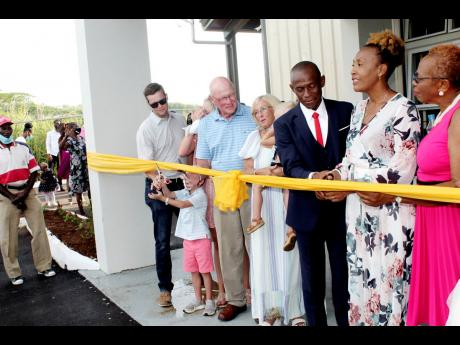 Pastor John Hines (third right) and his wife, Pastor Charlene (second right) cut the ribbon to signify the official opening of their newly constructed church – Abundant Life Ministry. Looking on from left are: Michael McSweeny, Brandi McSweeny, Rod McSwe