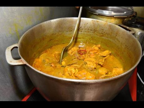 Tego gives his curried chicken a stir.