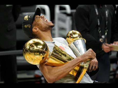 Milwaukee Bucks forward Giannis Antetokounmpo reacts while holding the NBA Championship trophy (left) and Most Valuable Player trophy after defeating the Phoenix Suns in Game Six of basketball's NBA Finals in Milwaukee on Tuesday night. The Bucks won 105