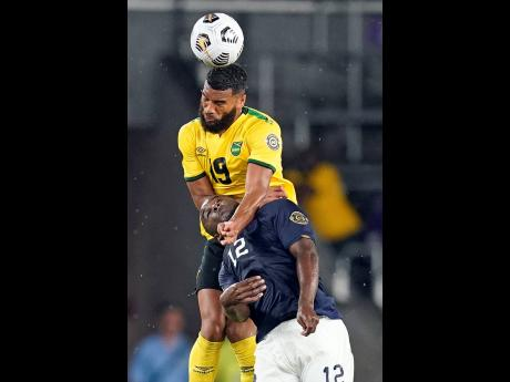 Jamaica defender Adrian Mariappa (top) beats Costa Rica forward Joel Campbell to a header during the second half of their Concacaf Gold Cup Group C match at Exploria Stadium in Orlando, Florida, on Tuesday.
