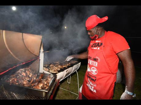 Desrick Hamilton paying close attention to the jerked chicken he would serve up for eager patrons.