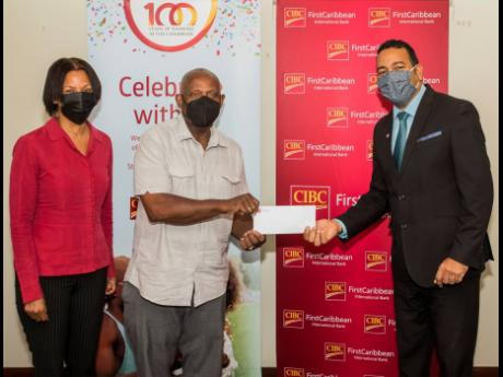 Nigel Holness (right), managing director, CIBC FirstCaribbean, presents a cheque to Lorenzo Ellis and Monica Walker for the Haile Selassie High School Incentive Programme.  The initiative targets grades seven to nine to encourage school attendance and assi