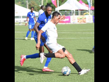 Mount Pleasant's Alwayne Harvey (front) comes under pressure from Molynes United's Jermy Nelson during their Jamaica Premier League game at the UWI/JFF Captain Horace Burrell Centre of Excellence on Sunday.