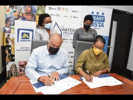 Parris Lyew-Ayee (left), chairman, JN Foundation and Novelette Denton-Prince (right), acting managing director, HEART/NSTA Trust sign a Memorandum of Understanding for academic programme enrichment, where the institution will offer courses in rainwater har