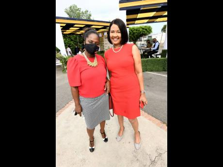 Bethune Lugg-Banton (right), general manager of QNet, and Andrea Messam, chairman, marketing, Cumax Wealth Management, at the unveiling of new signage and launch of Cumax Wealth Management.