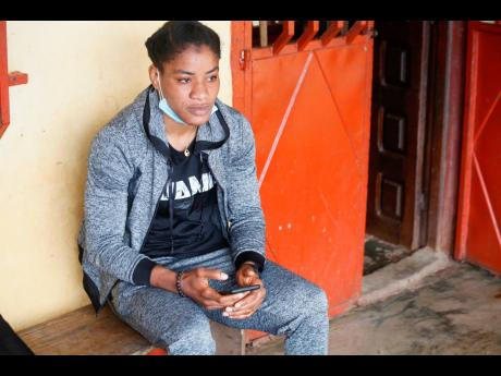 Fatoumata Yarie Camara, a Guinean freestyle wrestler scheduled to compete in the Tokyo Olympics, sits at her home in Conakry, Guinea, on Wednesday.