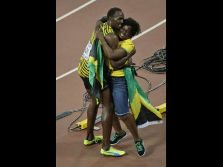Usain Bolt hugs his mom, Jennifer Bolt, after Usain won the men's 100m final at the World Athletics Championships at the Bird's Nest stadium in Beijing on Sunday, August 23, 2015.