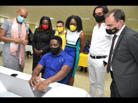 Coding student Richard Wilson demonstrates how to code for (from left) Fayval Williams, Minister of Education, Youth and Information; Kay-Marie Forbes-Robotham, Director, Strategic Partnerships Research and Innovation of HEART Trust/NTA; Andrew Pairman, CE