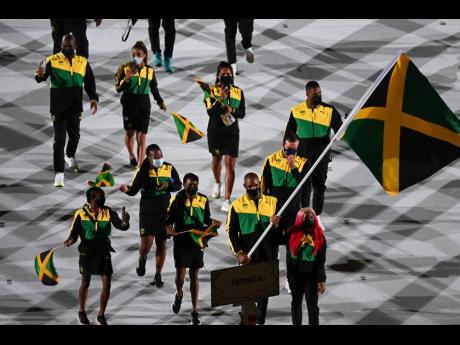 Team Jamaica, led by flag-bearers Ricardo 'Big 12' Brown (front second right), and Shelly-Ann Fraser-Pryce (front right), march into the Olympic Stadium during the opening ceremony of the Olympic Games in Tokyo, Japan on Friday morning.