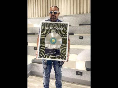 Sean Paul holds the plaque signifying his induction into Pandora's Billionaires' Club.