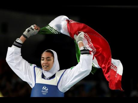 In this August 18, 2016 file photo, Kimia Alizadeh Zenoorin of Iran celebrates after winning the bronze medal in a women's Taekwondo 57-kg competition at the 2016 Summer Olympics in Rio de Janeiro, Brazil. The defector from Iran who left citing institut